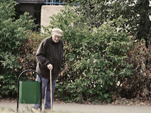 Russian seniors - poorly dressed old man with a walking canу looking into street garbage can Stock Photography