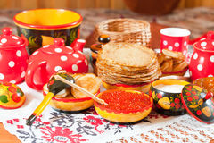 Russian Shrovetide meal - pancake. With caviar and tea royalty free stock photography