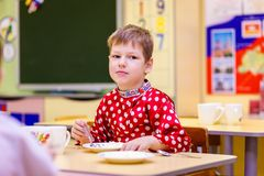 Russian six year old boy in red shirt eating in kindergarten, blurred background stock photo