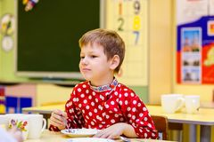 Russian six year old boy in red shirt eating in kindergarten, blurred background stock images