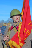 Russian soldier-reenactor holding a red flag Royalty Free Stock Photography