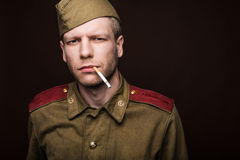 Russian soldier smoking cigarette and looks at som Stock Image