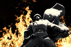 Russian Soldier Statue in Snow and Fire. Russian soldier covered in ice and snow with a flowing cape set against a flaming war style fire and black backdrop Stock Photos
