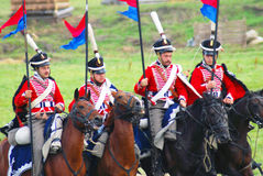 Russian soldiers-reenactors dressed in red ride horses. Stock Photo