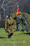 Russian soldiers-reenactors walk on the battle field. Stock Photos