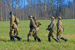Russian soldiers-reenactors walk on green grass Royalty Free Stock Photos