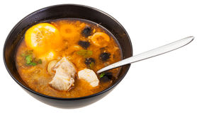 Russian Solyanka fish soup in bowl with spoon. Solyanka russian traditional spicy and sour soup with fish in bowl with spoon isolated on white background Royalty Free Stock Photo
