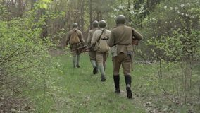 Russian Soviet Infantry Red Army Soldiers Of World War II Marching Walking Along Forest Road In Summer Day. Group of