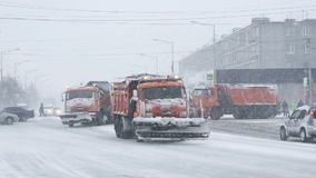 Russian special snow-clearing equipment trucks driving on road during snowfall blizzard stock footage