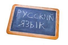 Russian is spoken written in russian. Sentence russian is spoken written in russian in a blackboard on a white background Stock Image