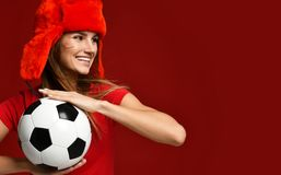 Russian style fan sport woman player in red uniform and ear-flap hat hold soccer ball celebrating happy smiling. Looking at the corner on red background stock photos