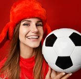 Russian style fan sport woman player in red uniform and ear-flap hat hold soccer ball celebrating happy smiling. On red background royalty free stock photography