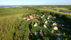 Russian summer village with wooden houses at sunset. Flying over roofs. Forests of northern Karelia, Russia Stock Photos