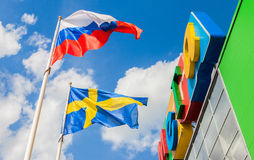 Russian and Sweden flags waving against the blue sky near the sh. ST. PETERSBURG, RUSSIA - JULY 28, 2016: Russian and Sweden flags waving against the blue sky Royalty Free Stock Photography