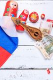 Russian symbols background. Russian symbols matryoshka, balalaika, rubles cash and flag of russian federation on wooden background Stock Photos