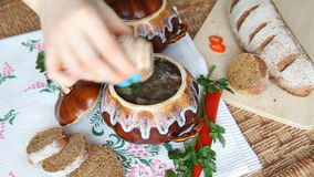 On the russian table is pot with lenten meal. Hand adds pepper to the soup. stock video footage