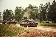 Russian tanks driving on a country road. Three russian tanks driving on a country road, dust clouds around Royalty Free Stock Photos
