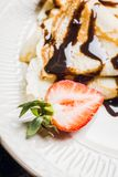 Russian thin pancakes blini, with strawberry and chocolate sauce. Selective focus royalty free stock photo
