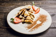 Russian thin pancakes blini, with strawberry and chocolate sauce. Selective focus royalty free stock image