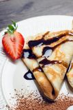 Russian thin pancakes blini, with strawberry and chocolate sauce. Selective focus royalty free stock images