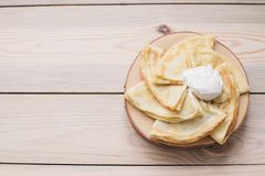 Russian thin pancakes on a wooden stand made of natural wood with sour cream . Maslenitsa is a Maslenitsa food festival. royalty free stock images