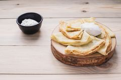 Russian thin pancakes on a wooden stand made of natural wood with sour cream . Maslenitsa is a Maslenitsa food festival. stock photography