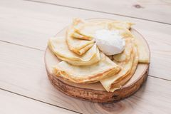 Russian thin pancakes on a wooden stand made of natural wood with sour cream . Maslenitsa is a Maslenitsa food festival. stock photo