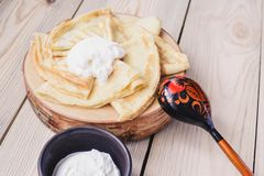 Russian thin pancakes on a wooden stand made of natural wood with sour cream . Maslenitsa is a Maslenitsa food festival. stock images