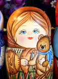 Russian toy. Matrioska. Matrioska representing a young girl with a toy bear. On sale in a christmas street market Royalty Free Stock Photos