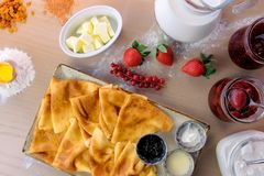 Russian traditional pancakes, blini served with jams, sour cream, and strawberry on the plate. Close-up top view. Russian traditional pancakes, blini served royalty free stock photo