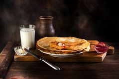 Pancakes with jam, butter and milk Stock Photography