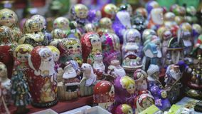 Russian Traditional Souvenirs. Many colorful Russian wooden souvenirs matrioshka, nesting dolls on the counter at a christmas fair stock footage