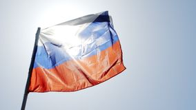 Russian flag flying in slow motion and back lit by the sun. Russian tricolor flag flying in slow motion and back lit by the sun stock video