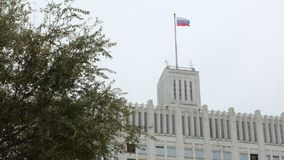 Russian tricolor flag is swaying by wind on top of government building of Russia in daytime. Tree is in side of frame stock video