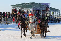 Russian Troika on the Racecourse during the national holiday. BELOKURIKHA, RUSSIA - MARCH 12, 2016: The Russian three of horses during the holiday Farewell to Stock Image