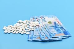 Russian two thousand rubles and round white pills on a blue background stock image