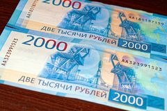 Russian two thousandth notes close-up against the background of a dark wooden table. Russian two thousandth notes close-up stock photo