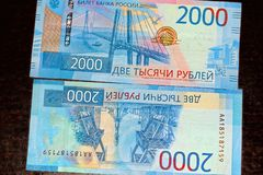 Russian two thousandth notes close-up against the background of a dark wooden table. Russian two thousandth notes close-up royalty free stock image