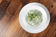 Russian and ukrainian traditional cold soup. Okroshka in a white plate. Wooden background Stock Images