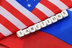 Russian and usa flag sanctions. Russian usa flag sanctions wooden letters on them stock image