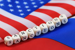 Russian and usa flag sanctions. Russian usa flag sanctions wooden letters on them royalty free stock image