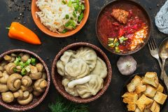 Russian variety of dishes, borsch, dumplings, pickled mushrooms, sauerkraut. Russian food on a rustic background, top view. royalty free stock image