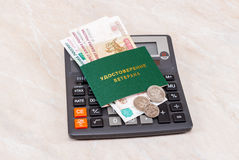 Russian Veteran Certificate with money lying over calculator. Te Royalty Free Stock Photography