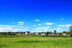 Russian village. Summer landscape of russian village with blue sky and green fields Royalty Free Stock Image