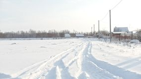 Russian village - snow-covered winter road at sunny day. Wide angle stock video footage