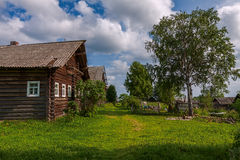 Russian village view. Summer view of traditional rustic russian village with wooden houses and birch tree Stock Photography