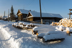 Russian village Visim in winter. Ural region, Russia. Snow-covered old wooden houses and heaps of firewood in a russian old believer village Visim. Ural region Royalty Free Stock Photography