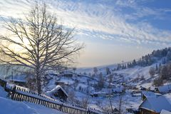 Russian Village in the Winter Forest in the Ural Mountains, Russia, Chelyabinsk region, Minyar. Pushkin`s fairy tal. Sunny winter day in the Ural Mountains Royalty Free Stock Photography