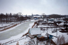 Russian village in winter with a frozen river and the Church Royalty Free Stock Photos