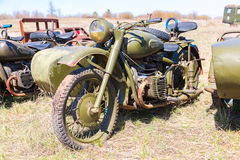 Russian vintage rusty motorcircle at the field in sunny day Stock Photos